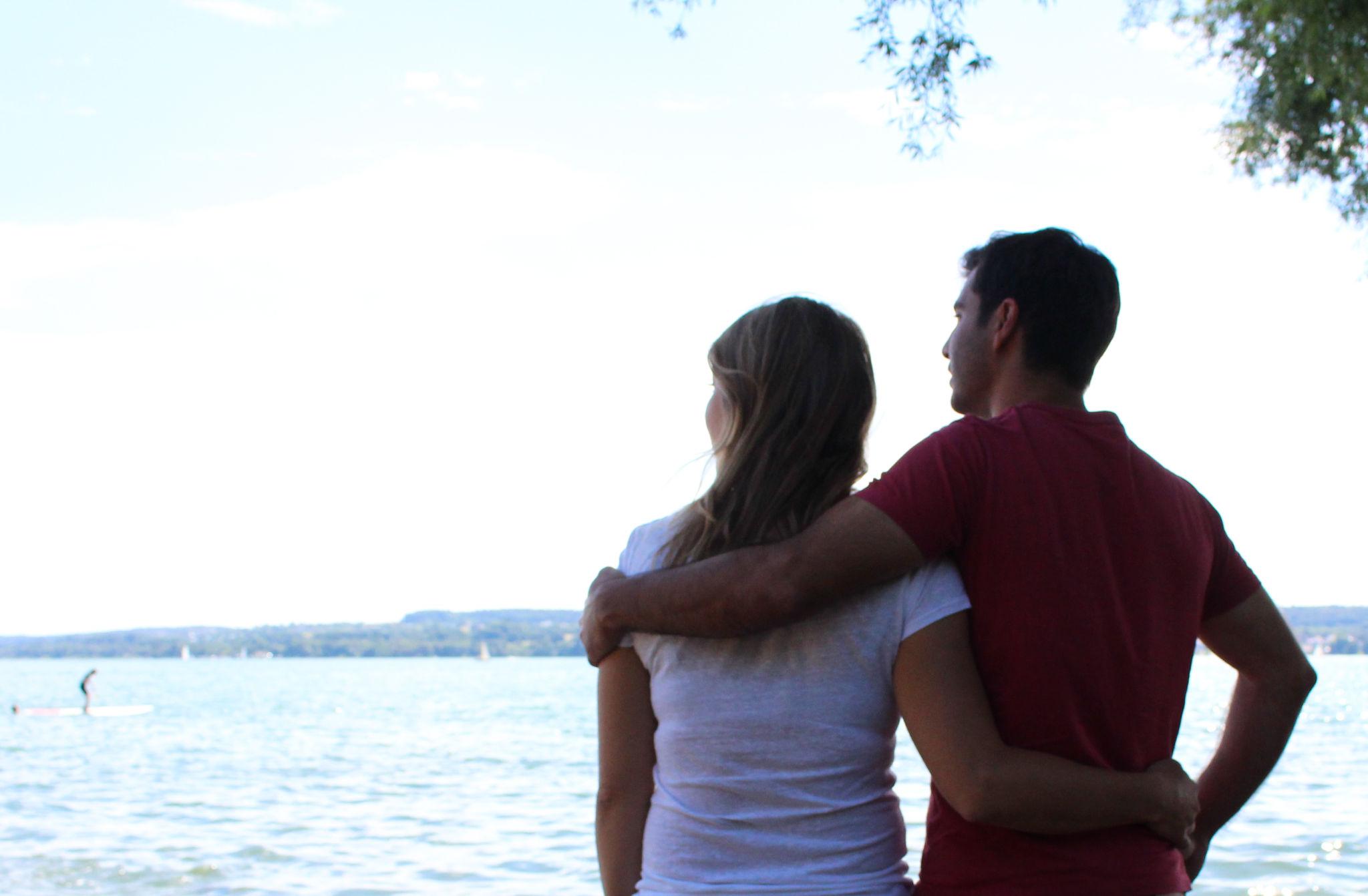 Pärchen am See legen Arm um einander Glück Liebe