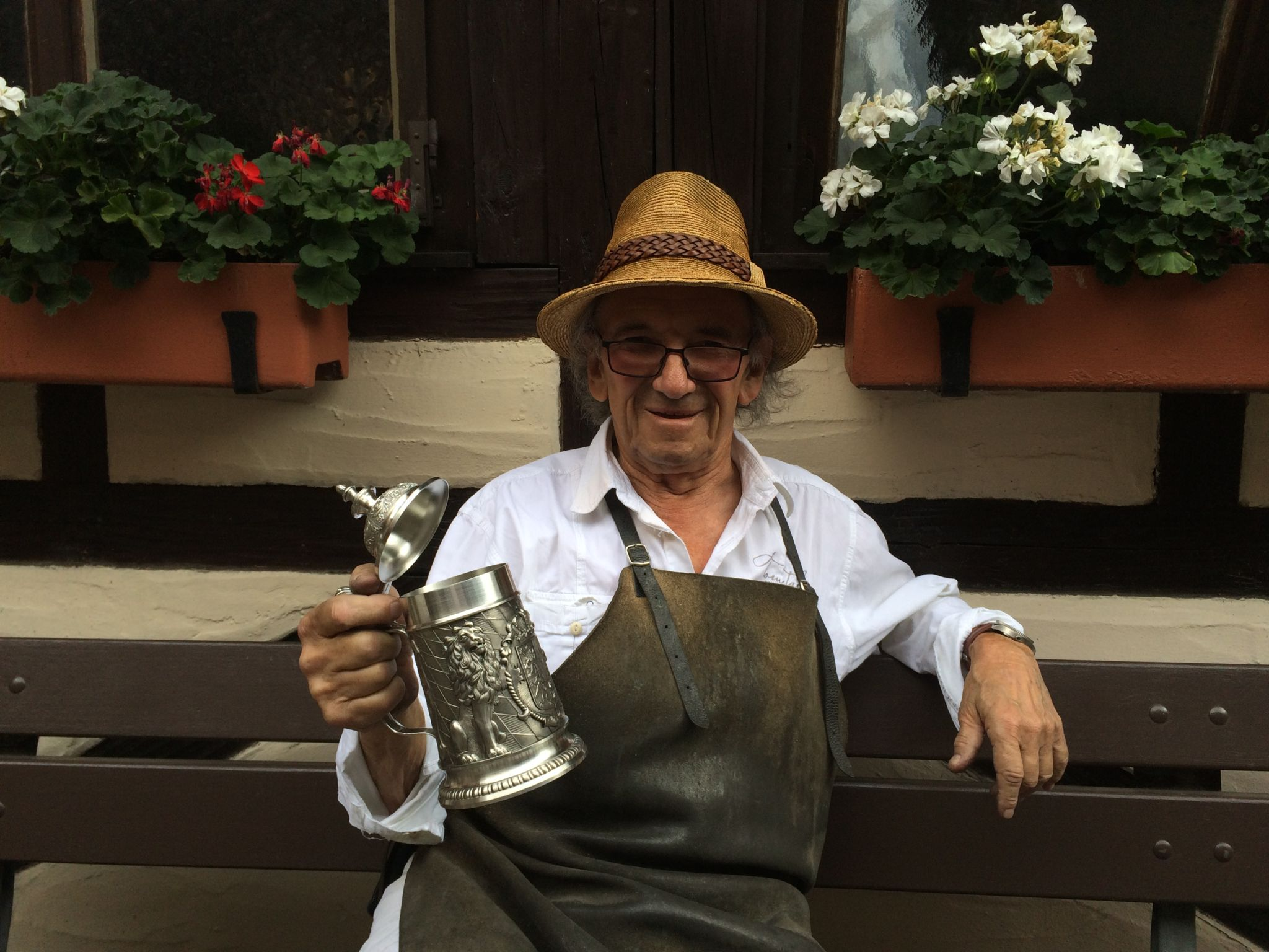 Alter Mann mit Zinnbierkrug auf Bank